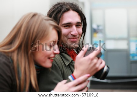 Young man showing digital photos on his camera to beautiful woman while walking down a street. - stock photo