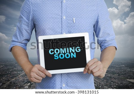 young man showing digital tablet with COMING SOON  in city , business concept ,business idea , analysis concept - stock photo
