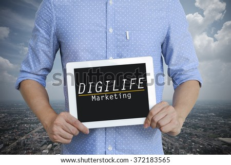 young man showing digital tablet with DIGILIFE MARKETING  on sky blackground  , business concept ,business idea - stock photo