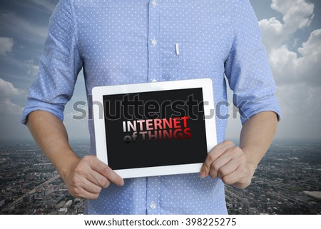 young man showing digital tablet with INTERNET OF THINGS  in city , business concept ,business idea , analysis concept - stock photo