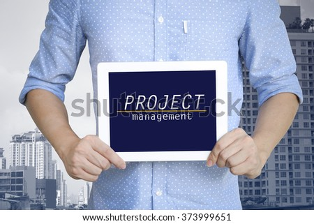 young man showing digital tablet with PROJECT MANAGEMENT  in city , business concept ,business idea - stock photo
