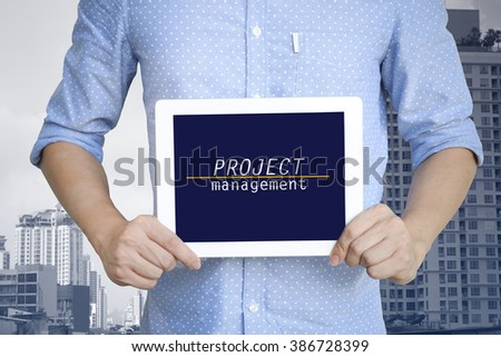 young man showing digital tablet with PROJECT MANAGEMENT in city  , business concept ,business idea , strategy concept - stock photo