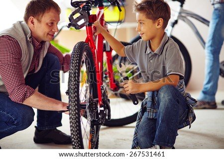 Young man showing his son how to repair bike - stock photo
