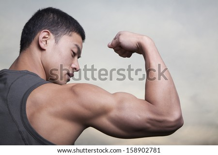 Young man showing off his bicep muscles