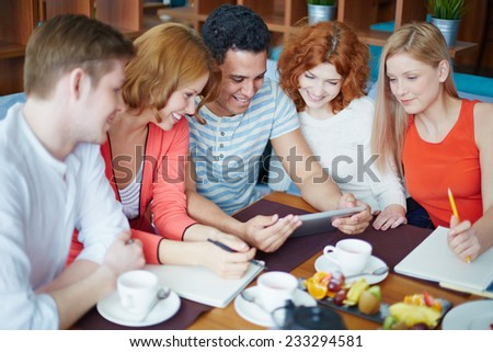 Young man showing photos on touchpad to his friends - stock photo
