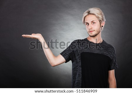 Young man showing presenting. Stylish guy holding empty hand palm copy space for product. Fashion, advertising concept. Studio shot on dark