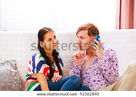 Young man showing shh... gesture to girlfriend while answering mobile phone