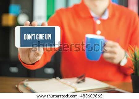 Young man showing smartphone and DON'T GIVE UP! word concept on screen