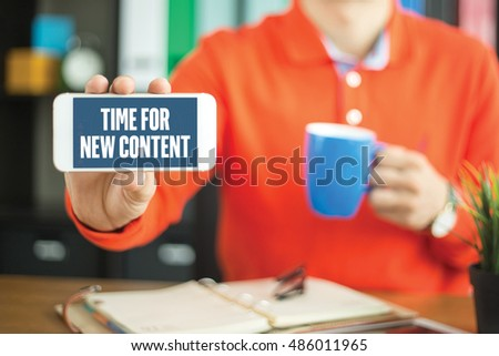 Young man showing smartphone and TIME FOR NEW CONTENT word concept on screen