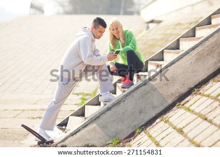 Young man showing something on the mobile phone to young woman next to him while exercising on the riverbank - stock photo