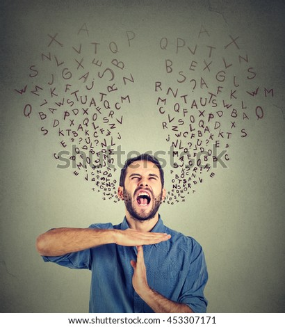 Young man showing time out hand gesture, frustrated screaming to stop alphabet letters coming out of mouth isolated on gray background. Too many things to do. Human emotions face expression reaction - stock photo