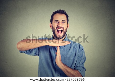 Young man showing time out hand gesture, frustrated screaming to stop isolated on grey wall background. Too many things to do overwhelmed. Human emotions face expression reaction - stock photo