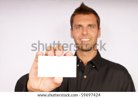 Young man shows business card. You can there write text. - stock photo