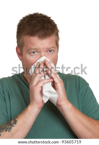 Young man sick with a cold blowing nose on tissue - stock photo