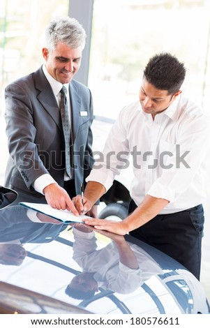 young man signing documents at car dealership with salesman - stock photo
