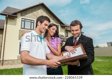 Young man signing renting contract with real estate agent. agent holding documents to sign agreement for house sale - stock photo