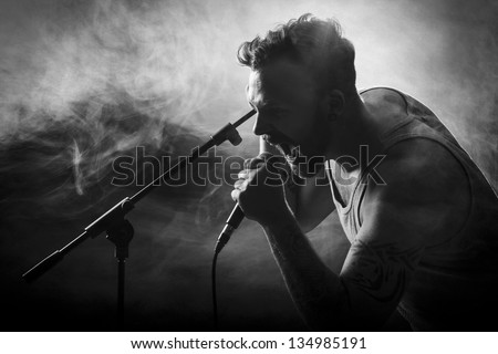 Young man sing / growls in hard rock concert. - stock photo