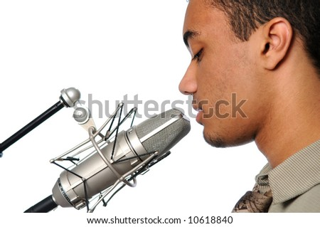 Young man singing into a vintage microphone - stock photo