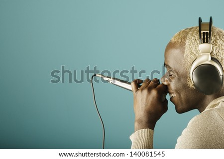 Young man singing into microphone - stock photo