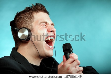 Young man singing into microphone. Happy karaoke signer studio shot blue background