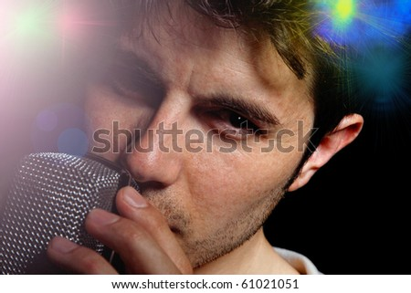 Young Man Singing over dark background - stock photo