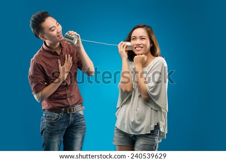 Young man singing to his girlfriend via tin phone - stock photo