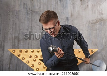 Young man singing with vintage microphone
