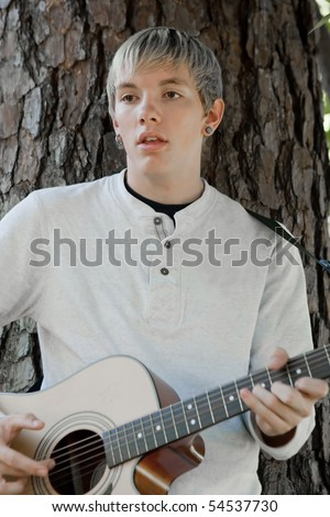 Young man sings and plays guitar outside leaning against a pine tree.