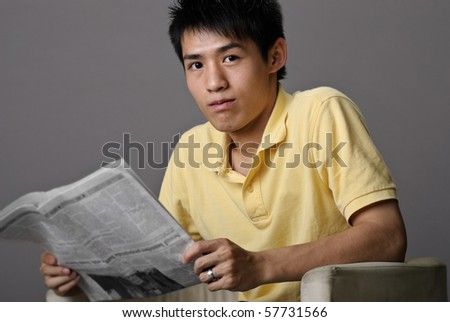 Young man sit on chair and read newspaper.
