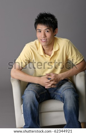 Young man sit on chair, closeup portrait over gray background.