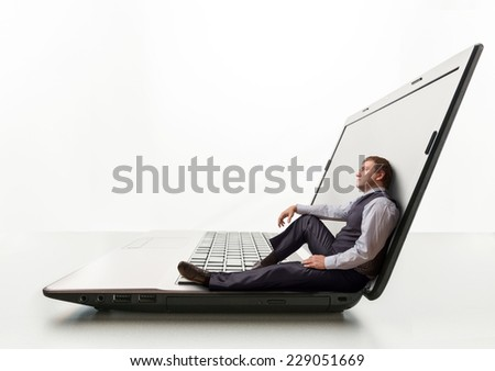 Young man sits on laptop - stock photo