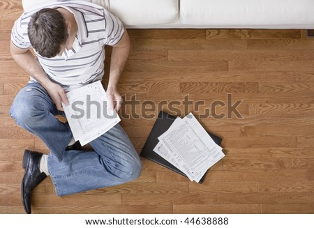 Young man sits on the floor as he looks through paperwork. Horizontal shot. - stock photo