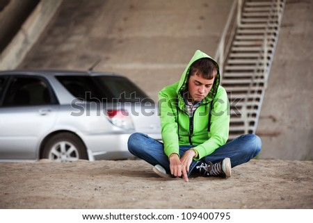 Young man sitting against a car - stock photo