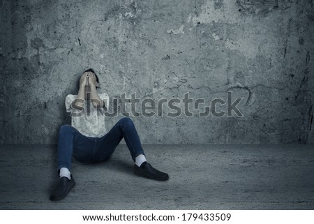 Young man sitting and leans on wall with fear - stock photo