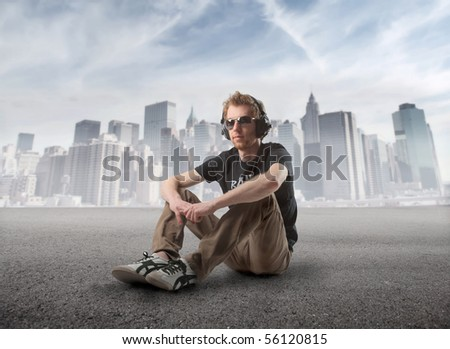 Young man sitting and listening to music with cityscape on the background - stock photo