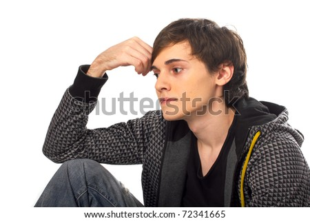 Young man sitting and thinking looking away from camera