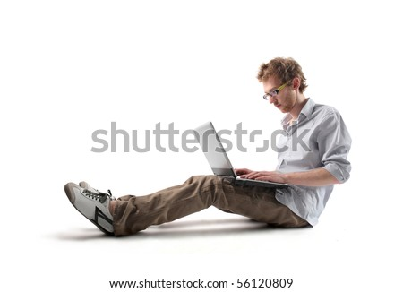 Young man sitting and using a laptop - stock photo