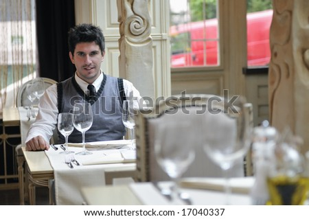 Young man sitting and waiting food at stylish restaurant - stock photo