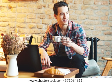 Young man sitting at a cafe, using a laptop, drinking espresso - stock photo
