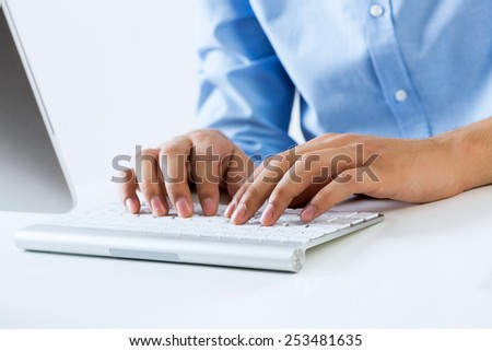 Young man sitting at desk and typing on keyboard