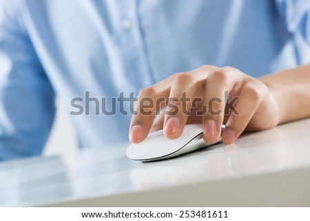 Young man sitting at desk and typing with mouse
