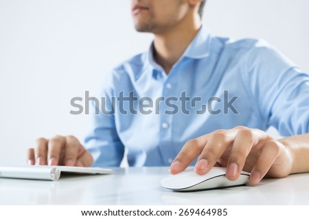 Young man sitting at desk and working on computer - stock photo