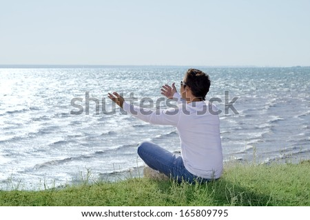 young man  sitting at precipice and looking on the sea shore - stock photo