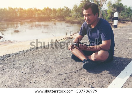 young man sitting at runway after jogging and listening music with his smartphone.