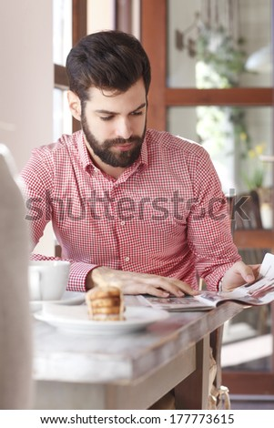 Young man sitting at table and reading newspaper in coffee shop. - stock photo