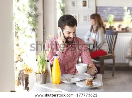 Young man sitting at table and using his smartphone in coffee shop. - stock photo