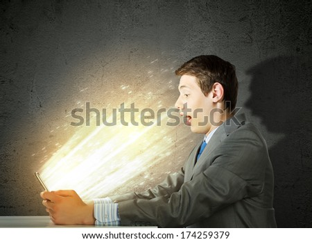 Young man sitting at table and using laptop