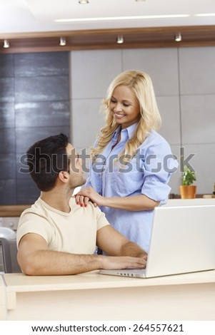 Young man sitting at table at home, using laptop computer, woman touching shoulder, smiling. - stock photo