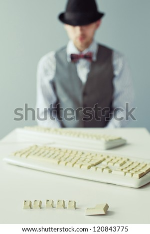 Young man sitting at the table with keyboard in a hat and bow-tie - stock photo