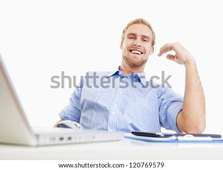 young man sitting behind desk at the office smiling